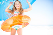 Happy girl on beach with orange floating tyre