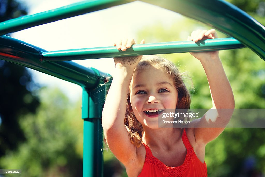 Happy girl on monkey bars