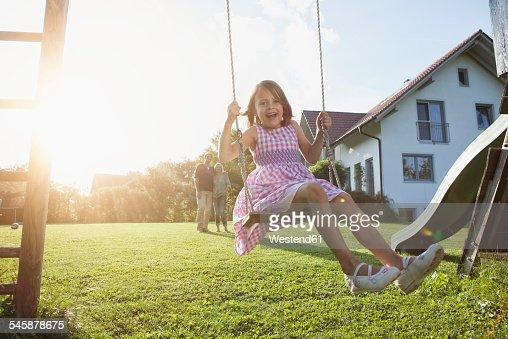 Happy girl on swing in garden