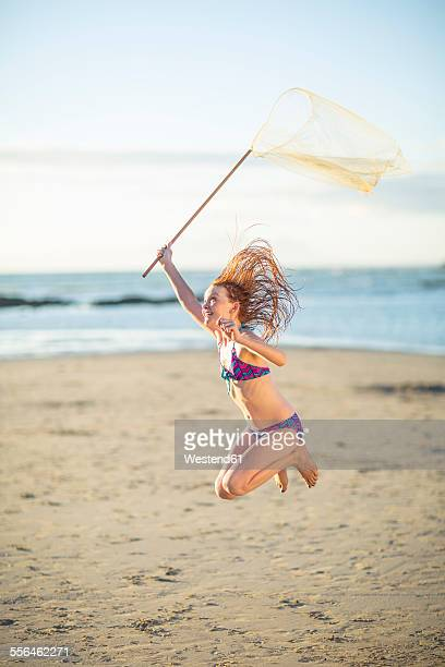 Happy girl on the beach jumping with a butterfly net
