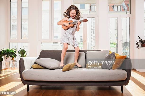 Happy girl playing mini guitar while jumping on a couch in living room at home