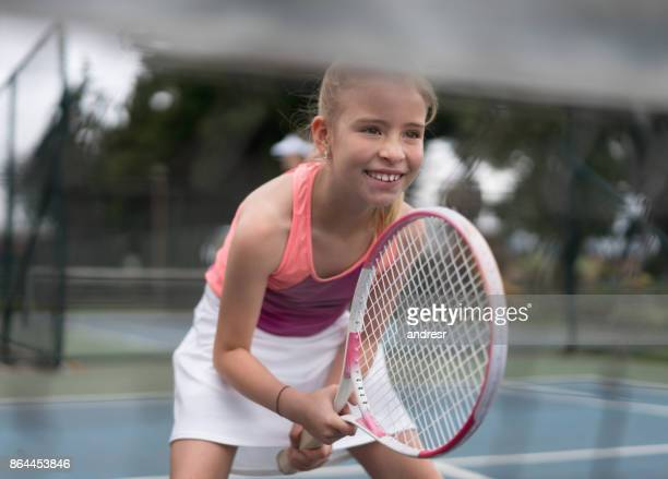 Happy girl playing tennis and holding her racket