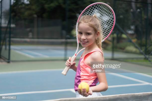 Happy girl playing tennis and looking at the camera