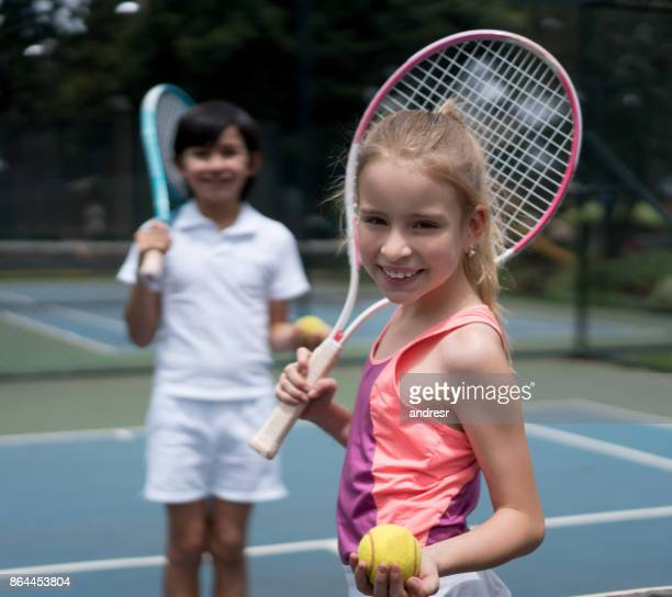 Happy girl playing tennis outdoors with a friend