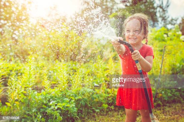 Happy girl playing with water in summer