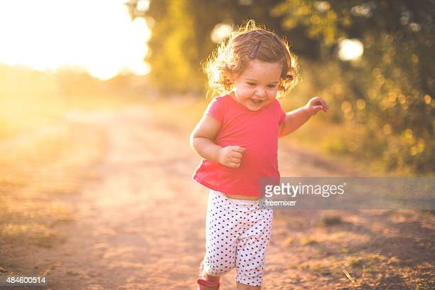 Happy girl running on a dusty road