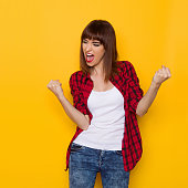 Young woman in red lumberjack shirt and jeans shouting clenches fists and looking away. Three quarter length studio shot on yellow background.