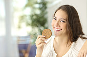 Happy girl showing a dietetic cookie sitting on a couch at home