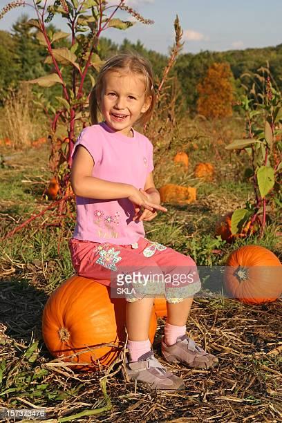 Fröhliche Mädchen sitzt auf einem Kürbis in pumkin Aufnäher