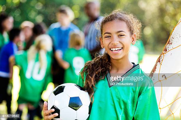 Happy girl smiles after winning soccer game