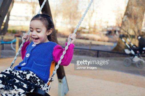 Happy girl swinging : Stock Photo