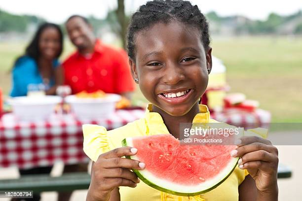 Happy Girl Taken Bite Out of Watermelon at Family Picnic