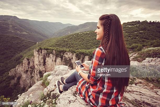 Fille heureuse envoyer des SMS sur le sommet de la montagne