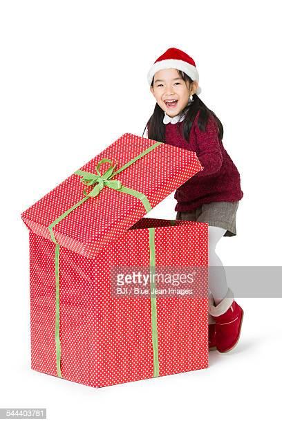 Happy girl unwrapping Christmas gift