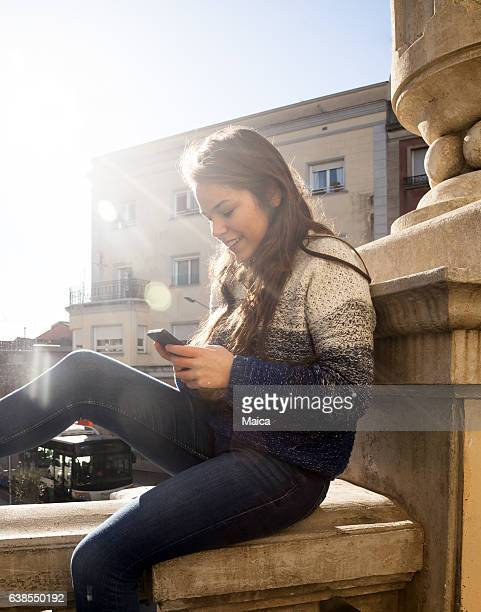 Happy girl using mobile in the city street
