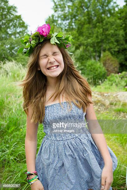 Happy girl wearing wreath of flowers, Nykoping, Sodermanland, Sweden