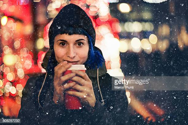 Happy girl with cup of coffee under the snow