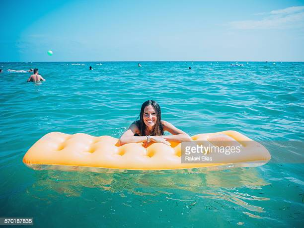 Happy girl with inflatable beach mattress