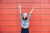 Happy young woman with raised hands against red wall