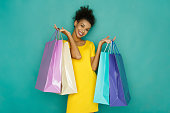Happy black girl with shopping bags. Excited smiling shopaholic holding colorful shopping bags at turquoise sudio background with copy space