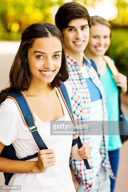 Happy Girl With Students Standing In A Row On Campus