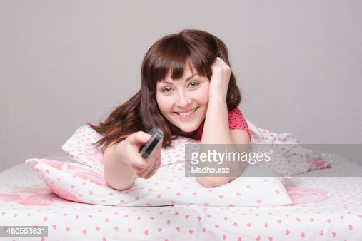 Happy girl with the remote in bed watching TV : Stock Photo