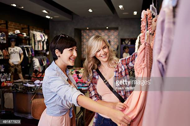 Happy girlfriends looking at dress in fashion shop