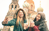 Happy girlfriends taking winter selfie at ' Savior on Spilled Blood ' church in Saint Petersburg - Friendship concept with girls having fun together drinking coffee outdoor - Focus on left young woman