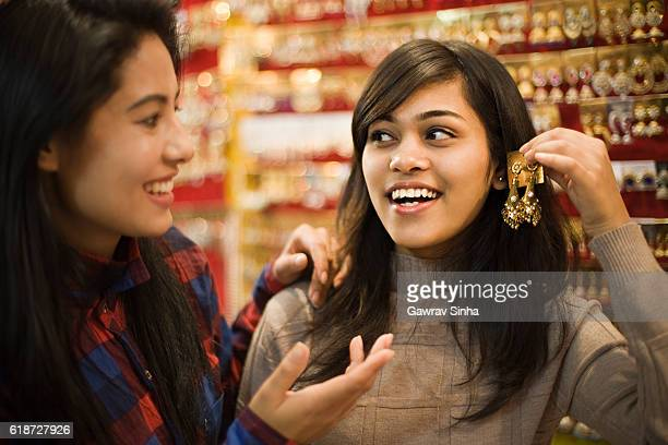 Happy girls buying earrings in jewelry shop before festival.