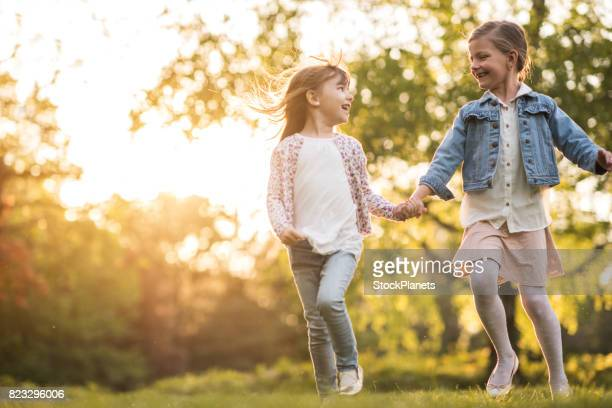 Happy girls having fun while running in the park at sunset.