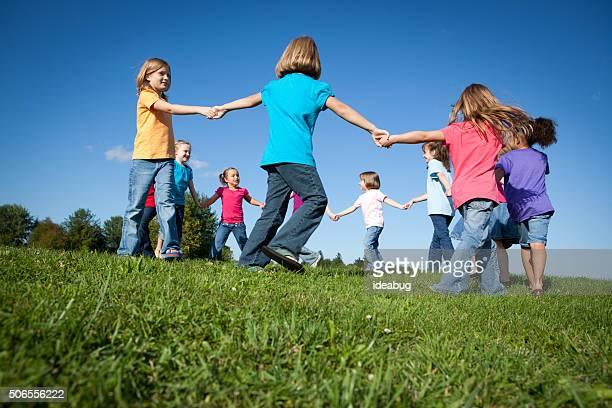 Felice bambina con le mani in cerchio esterno, amicizia, unità