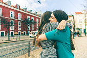 Happy girls hugging in Lisbon. Two women, best friends, meeting and embracing on a sunny spring day. Friendship and lifestyle concept, real people.