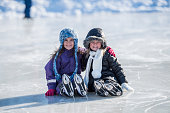 Two girls are outdoors on a cold winter day. They are dressed in warm clothing. They are taking a break from skating. They are sitting together on a frozen pond and embracing while smiling at the came