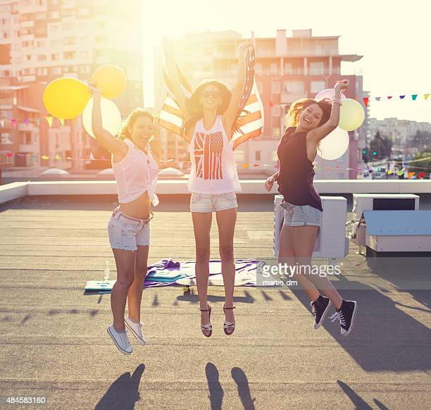 Happy girls jumping from joy on the rooftop