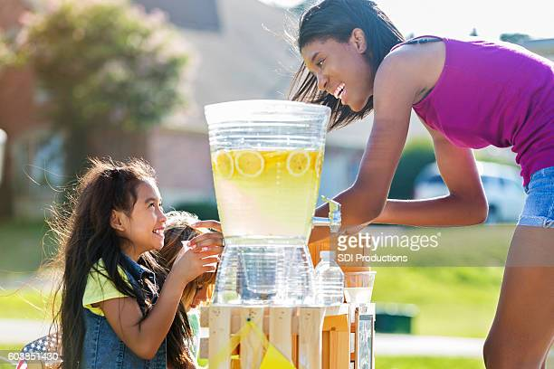 Happy girls sell lemonade to adult customer