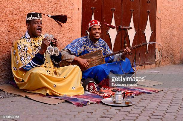 Happy Gnawa street musicians in Marrakech swinging their tarboosh tassels in time