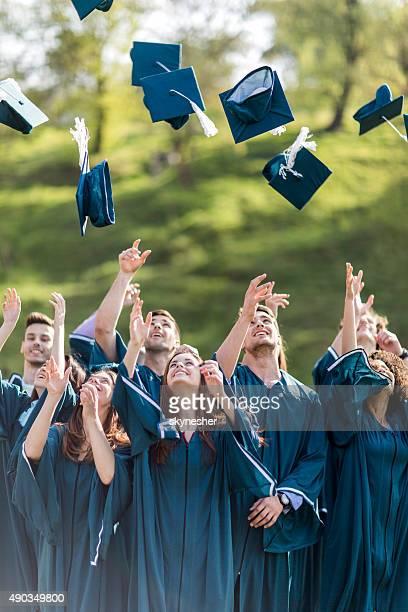 幸せな学生の卒業の帽子投げるすり鉢ボードをどうぞ。
