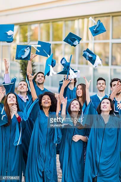 Felice studenti gettare il Tocco accademico cappelli laurea nell'aria.