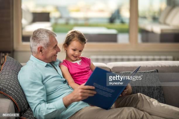 Glückliche Großvater und Enkelin genießen in buchen zu Hause lesen.