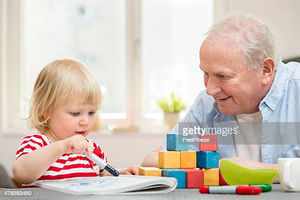 Happy grandfather and granddaughter together at home