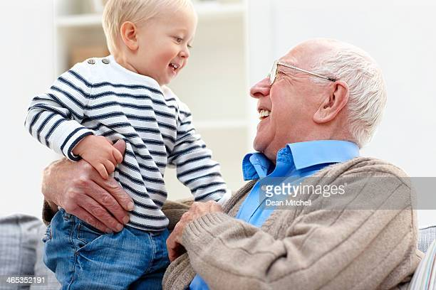 Happy grandfather and grandson together at home