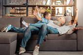 Sweet moments. Happy loving grandfather bonding to his grandchildren and goofing around with them on the couch