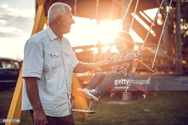 Happy grandfather swinging his grandson at sunset.
