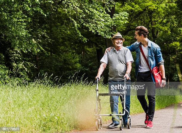 Happy grandfather walking with his grandson in nature