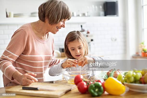 Feliz abuela y granddaughter cocinar alimentos