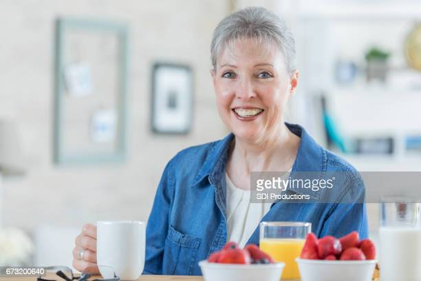Happy grandmother enjoys breakfast at home
