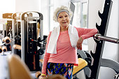 Outgoing old woman leaning on tool. She pumping iron in exercise room. Portrait