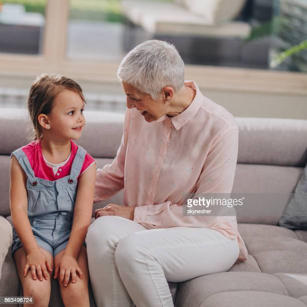 Happy grandmother talking to her granddaughter on sofa at home.