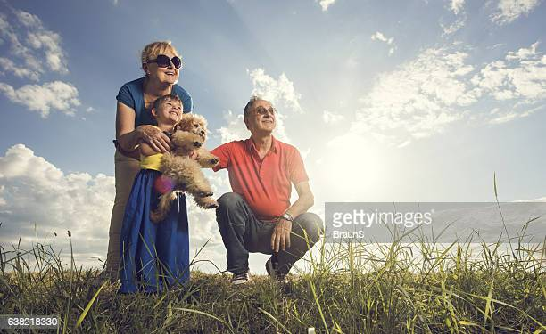 Happy grandparents and grandchild with a dog in nature.
