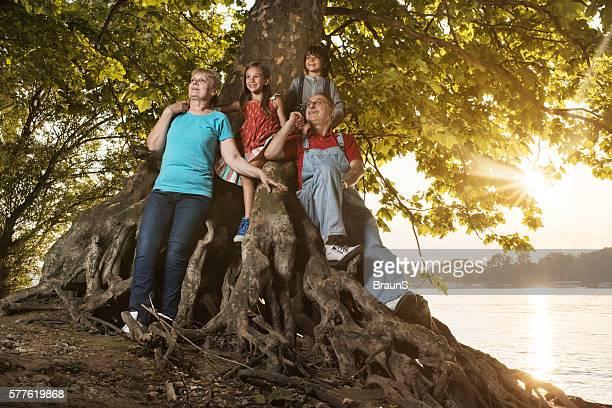 Happy grandparents and grandchildren having fun on the tree.